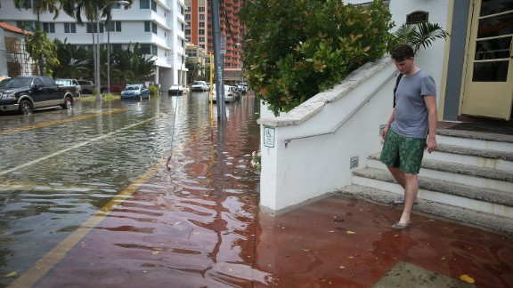 MIAMI BEACH, FL - SEPTEMBER 29:  A hotel guest steps out of a hotel into a flooded street that was caused by the combination of the lunar orbit which caused seasonal high tides and what many believe is the rising sea levels due to climate change on September 29, 2015 in Miami Beach, Florida. The City of Miami Beach is in the middle of a five-year, $400 million storm water pump program and other projects that city officials hope will keep the ocean waters from inundating the city as the oceans rise even more in the future.  (Photo by Joe Raedle/Getty Images)
