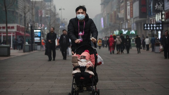 A Chinese man and his child wear masks to protest against pollution as they walk through a shopping area in heavy smog on December 8, 2015 in Beijing, China.