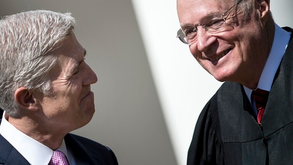 Neil Gorsuch (L) smiles at Supreme Court Justice Anthony Kennedy before taking the judicial oath during a ceremony in the Rose Garden of the White House April 10, 2017 in Washington, DC. / AFP PHOTO / Brendan Smialowski
