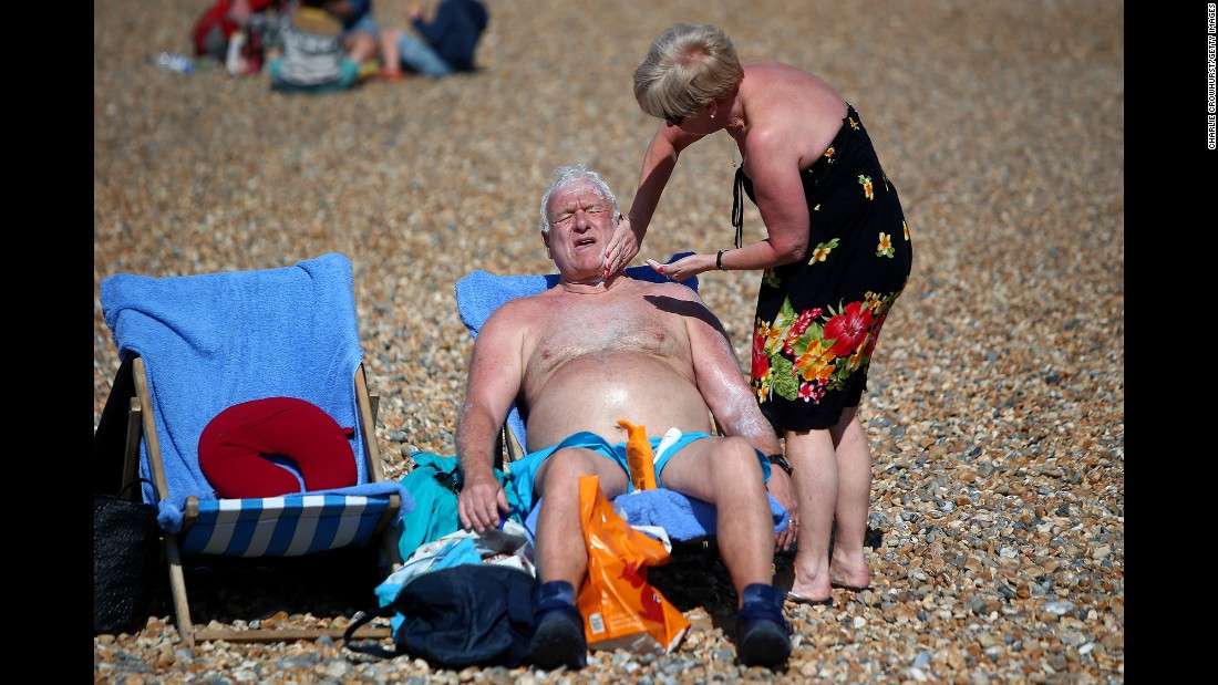 A woman rubs sunscreen on a man as they relax on a beach in Brighton, England, on Sunday, April 9.