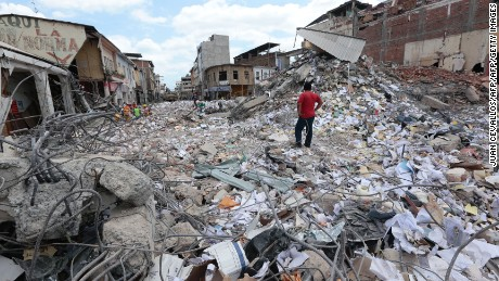 TOPSHOT - A man stares at the rubble in Portoviejo, Ecuador on April 20, 2016. The death toll from Ecuador's earthquake was set to rise sharply after authorities warned that 1,700 people were still missing and anger gripped families of victims trapped in the rubble. A 6.1-magnitude earthquake struck off the coast of Ecuador Wednesday, sowing new panic four days after a more powerful quake killed more than 525 people, with hundreds still missing. / AFP / Juan Cevallos        (Photo credit should read JUAN CEVALLOS/AFP/Getty Images)