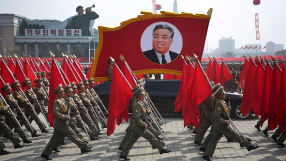 North Korean soldiers carry flags and a photo of late leader Kim Il Sung as they march across Kim Il Sung Square during a military parade on Saturday.