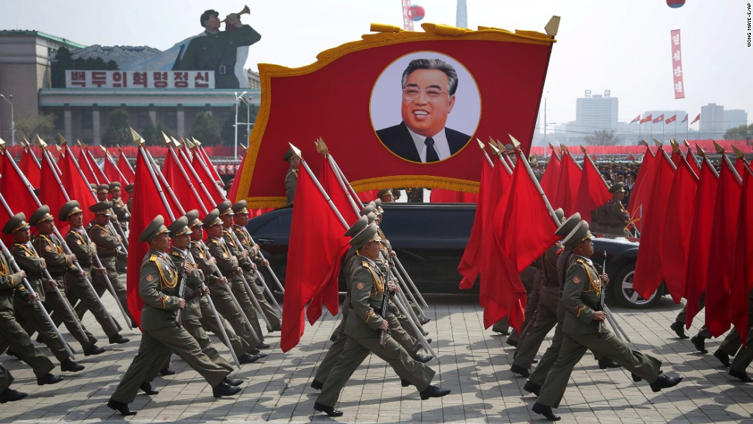 North Korean soldiers carry flags and a photo of late leader Kim Il Sung as they march across Kim Il Sung Square.