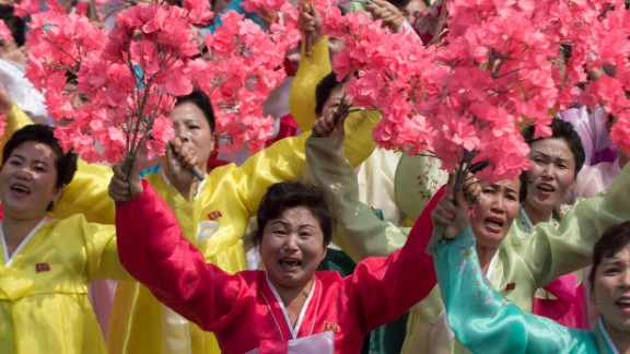 Women wearing traditional Korean dress wave flowers and shout slogans as they pass North Korea