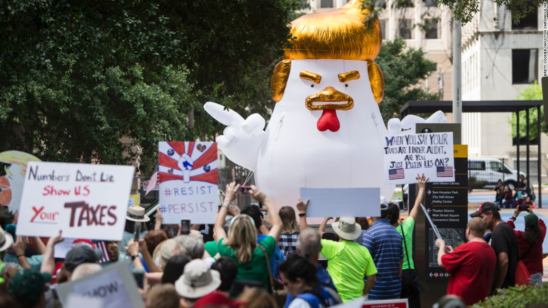 Demonstrators march through downtown Houston demanding greater governmental transparency and the release of President Donald Trump's tax returns.
