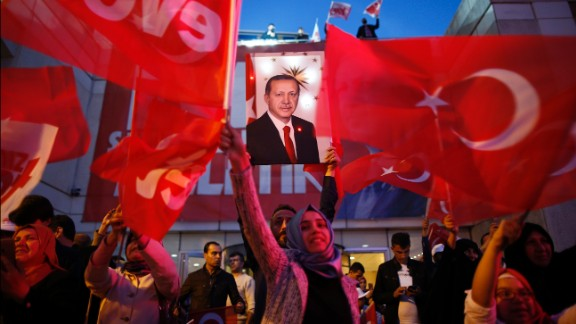 Supporters of Justice and Development party wave Turkish flags and hold a poster of Turkish President Recep Tayyip Erdogan outside its offices in Istanbul, Sunday, April 16, 2017.