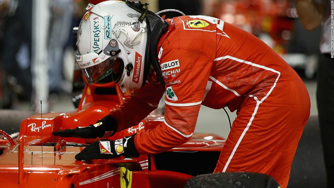 "Vettel pats his car -- which he has christened ""Gina"" -- in parc ferme after winning in Bahrain."