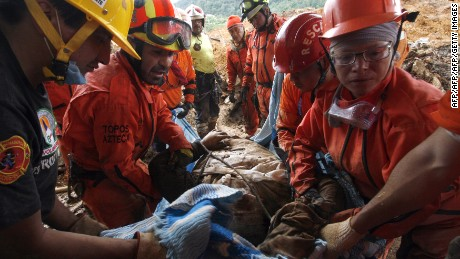 "Mexican rescue team ""Topos"" (Moles) personnel dig out the body a the victim of a landslide in La Pintada, Guerrero state, Mexico on September 22, 2013. Mexico looked Saturday to the Herculean task of rebuilding after a rare double onslaught of storms, with at least 170 people feared dead in the path of destruction.  AFP PHOTO/ Pedro Pardo        (Photo credit should read Pedro PARDO/AFP/Getty Images)"