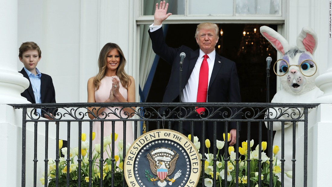 President Donald Trump waves to guests after delivering remarks from the Truman Balcony alongside first lady Melania Trump and their son Barron.