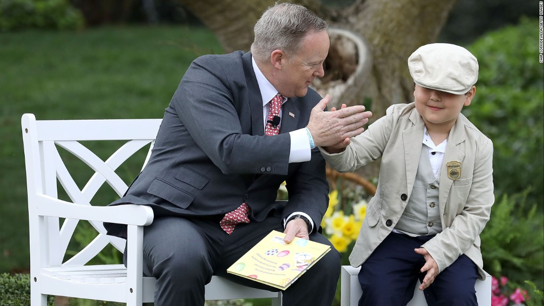 "White House Press Secretary Sean Spicer gets a high-five from a boy who sat next to him while he read the childrens' book, ""How To Catch The Easter Bunny."""