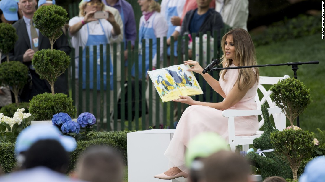 First lady Melania Trump reads a book to guests at the 139th White House Easter Egg Roll.