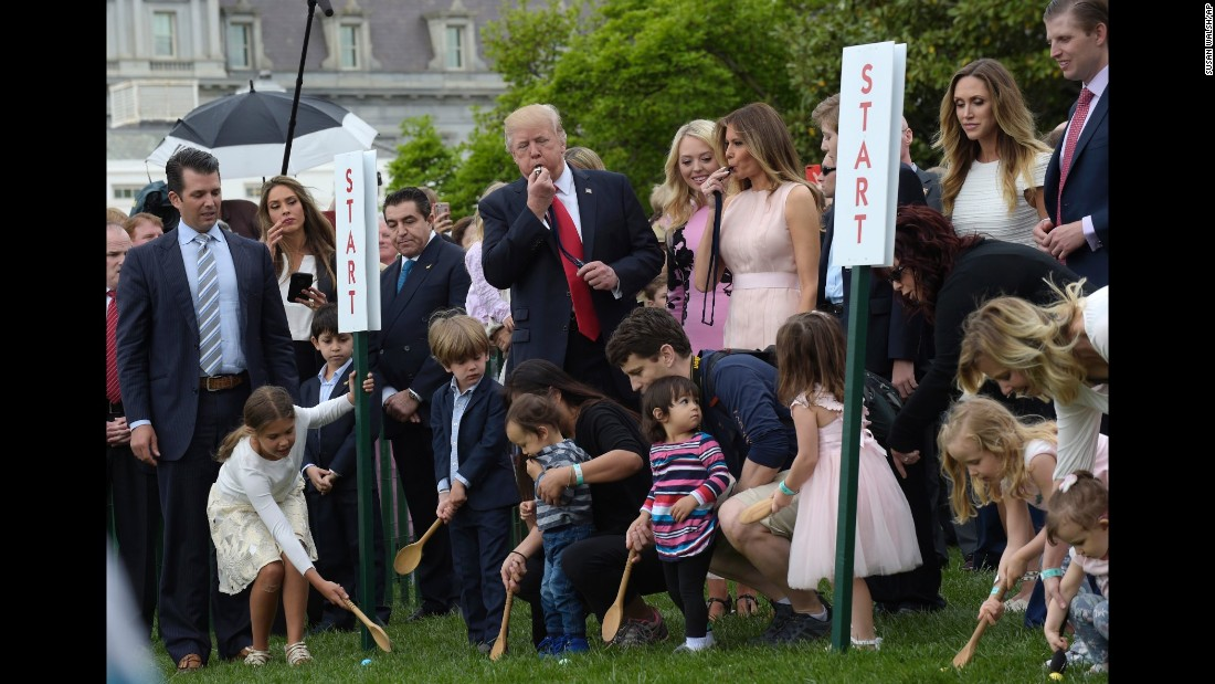 President Donald Trump and first lady Melania Trump blow whistles to begin an Easter Egg Roll race.