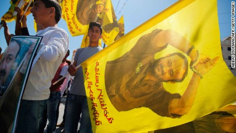 Protesters wave flags bearing a portrait of Marwan Barghouti during a rally in Ramallah Monday.