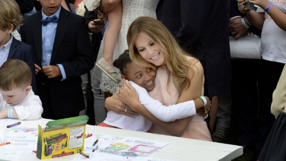 The first lady hugs a child at the annual White House Easter Egg Roll in April 2017. They were making cards for members of the US military.
