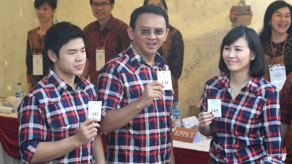 Ahok flanked by his wife Veronica (R) and son Nicholas (L) show off their first-round ballot papers  in Jakarta on February 15.