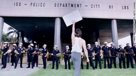 LOS ANGELES, CA - APRIL 30:  A demonstrator protesting the 29 April 1992 verdict in the trial of four Los Angeles police officers accused of beating motorist Rodney King holds a placard aloft before a line of police as protesters gathered at the Parker Center, the headquarters of the Los Angeles Police Department.  (Photo credit should read AFP PHOTO MIKE NELSON/AFP/Getty Images)