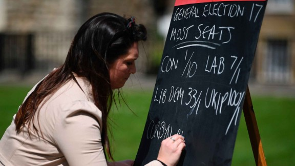 An employee from a betting company writes odds on a blackboard outside the Houses of Parliament.