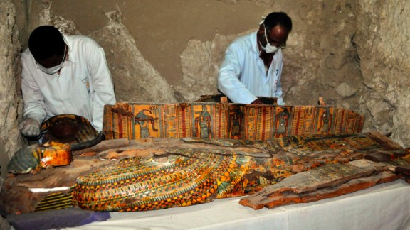 TOPSHOT - Members of an Egyptian archaeological team work on a wooden coffin discovered in a 3,500-year-old tomb in the Draa Abul Nagaa necropolis, near the southern Egyptian city of Luxor, on April 18, 2017.