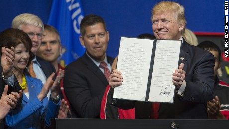 US President Donald Trump holds up a Buy American, Hire American Executive Order after signing at Snap-On Tools in Kenosha, Wisconsin, April 18, 2017. / AFP PHOTO / SAUL LOEB        (Photo credit should read SAUL LOEB/AFP/Getty Images)