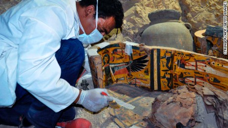 A member of the Egyptian archaeological team works on a wooden coffin Tuesday.