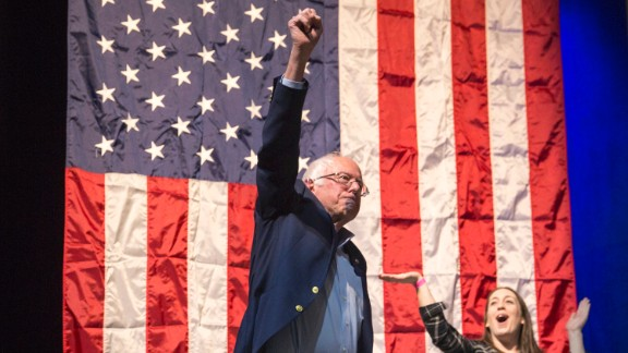 "In this April 17, 2017 photo former presidential candidate Bernie Sanders greets the crowd at a packed State Theatre before his speech at the ""Come Together and Fight Back"" tour in Portland, Maine. Sanders called for a radical transformation of the Democratic Party into a grassroots movement founded on the tenets of his unsuccessful Democratic presidential campaign: fighting against the billionaire class and rigged economic and political systems."