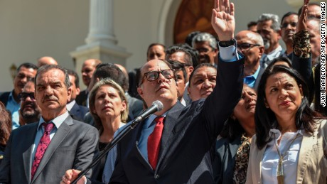 "The president of Venezuela's National Assembly, Julio Borges (C), accompanied by opposition deputies, reads a statement in Caracas on April 18, 2017. Most of the Venezuelan parliament on Tuesday asked the Armed Forces to stop ""repression"" in opposition demonstrations and be loyal to the Constitution, on the eve of a huge rally convened against President Nicolas Maduro. Maduro's supporters and opponents will stage rallies on Wednesday in Venezuela's increasingly violent political standoff and economic crisis. / AFP PHOTO / Juan BARRETO        (Photo credit should read JUAN BARRETO/AFP/Getty Images)"