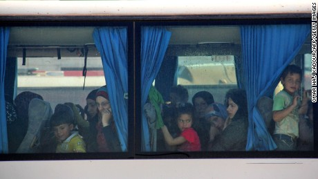 Women and children look out from a bus window.