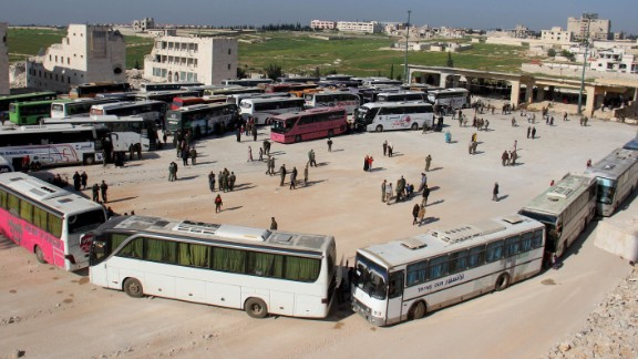 Syrians board a convoy of buses.