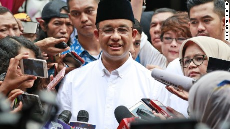Likely gubernatorial winner Anies Baswedan, center, faces reporters Wednesday after voting in Jakarta.