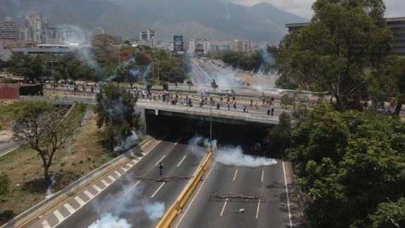 Clouds of tear gas spread across a highway in Caracas during clashes on Monday, April 10.