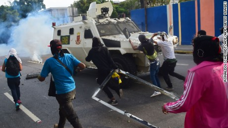 Demonstrators attack a National Guard vehicle in clashes during a rally against Venezuelan President Nicolas Maduro, in Caracas on April 19, 2017. Venezuelans took to the streets Wednesday for massive demonstrations for and against President Nicolas Maduro, whose push to tighten his grip on power has triggered deadly unrest that has escalated the country's political and economic crisis. / AFP PHOTO / RONALDO SCHEMIDT        (Photo credit should read RONALDO SCHEMIDT/AFP/Getty Images)