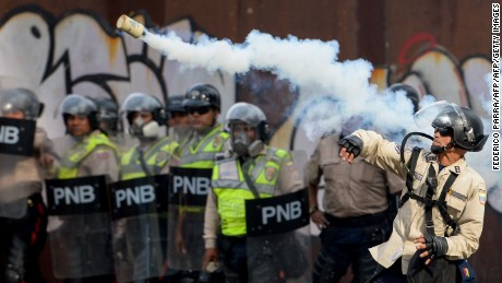 A riot policeman throws a tear gas canister at demonstrators during a rally against Venezuelan President Nicolas Maduro, in Caracas on April 19, 2017. Venezuela braced for rival demonstrations Wednesday for and against President Nicolas Maduro, whose push to tighten his grip on power has triggered waves of deadly unrest that have escalated the country's political and economic crisis. / AFP PHOTO / FEDERICO PARRA        (Photo credit should read FEDERICO PARRA/AFP/Getty Images)