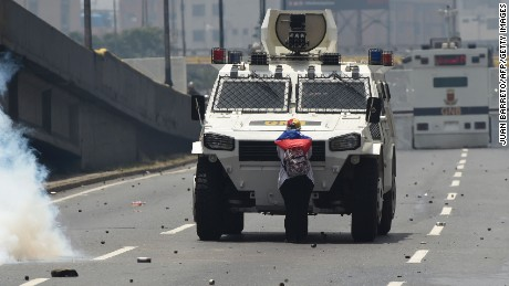 A demonstrator stands in front of an armoured vehicle of the riot police during a rally against Venezuelan President Nicolas Maduro, in Caracas on April 19, 2017. Clashes broke out Wednesday at massive protests against Maduro, as riot police fired tear gas to push back stone-throwing demonstrators and a young protester was shot dead. Violence erupted when thousands of opposition protesters tried to march on central Caracas, a pro-government bastion where red-clad Maduro supporters were massing for a counter-demonstration.  / AFP PHOTO / Juan BARRETO        (Photo credit should read JUAN BARRETO/AFP/Getty Images)