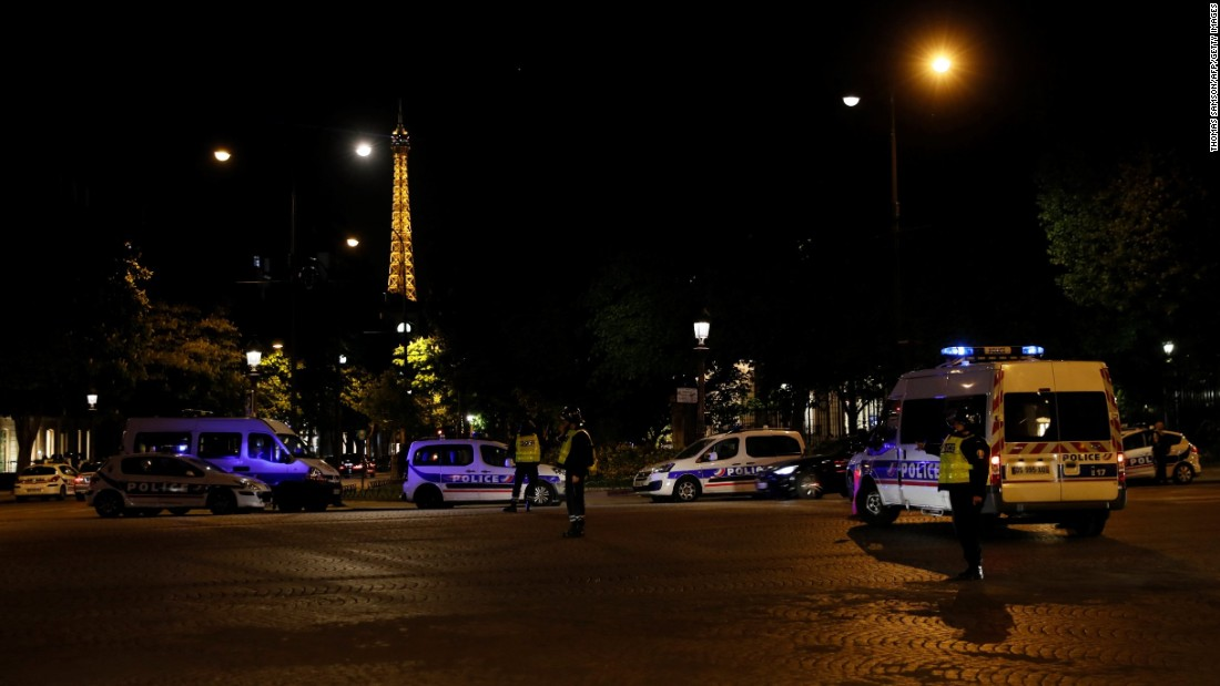 The Eiffel Tower is seen in the background as police officers block the entrance to the Champs-Elysées.