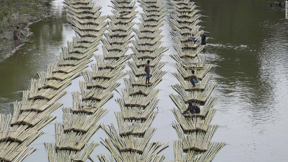 Indian laborers transport bamboo logs down the Longai River in Damchara, India, on Tuesday, April 18.