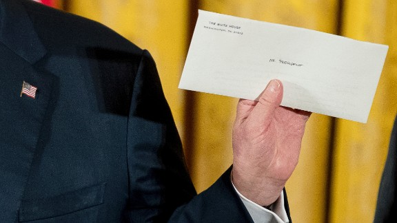 """Trump holds up a letter Sunday, January 22, that was left for him by former President Barack Obama. """"I just went to the Oval Office and found this beautiful letter from President Obama. It was really very nice of him to do that. And I will cherish that,"""" said Trump, who frequently criticized Obama on the campaign trail. Trump wouldn't tell the press what was in the letter."""