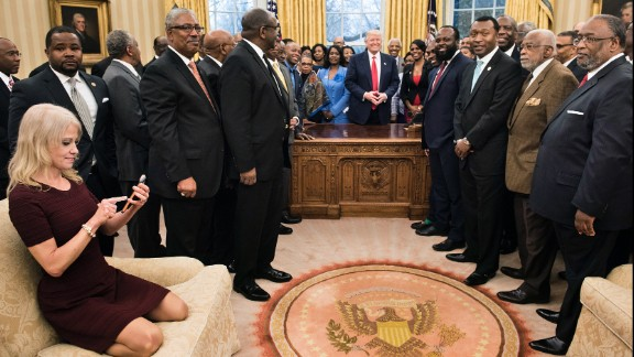 White House Adviser Kellyanne Conway takes an Oval Office photo of Trump and leaders of historically black colleges and universities on Monday, February 27. The image of her kneeling on the couch sparked memes on social media.