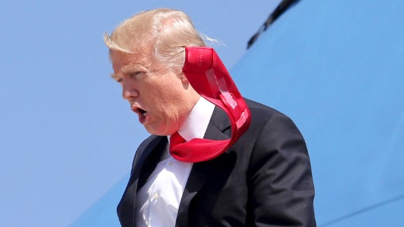 A strong wind blows Trump's tie as he arrives at Orlando International Airport on March 3. CNN's Jeanne Moos reports on Trump's presidential neckwear: Long ties with Scotch tape on the back