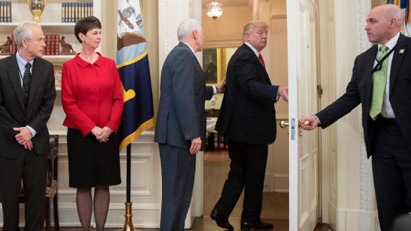 Vice President Mike Pence, third from left, tries to stop Trump as Trump walks out of an executive order signing ceremony on Friday, March 31. During the signing ceremony, White House pool reporters asked Trump questions about former national security adviser Michael Flynn, who has offered to testify on Russian involvement in the US election. The President ignored the questions and moved to another room to sign the two executive orders, which regarded trade policy.