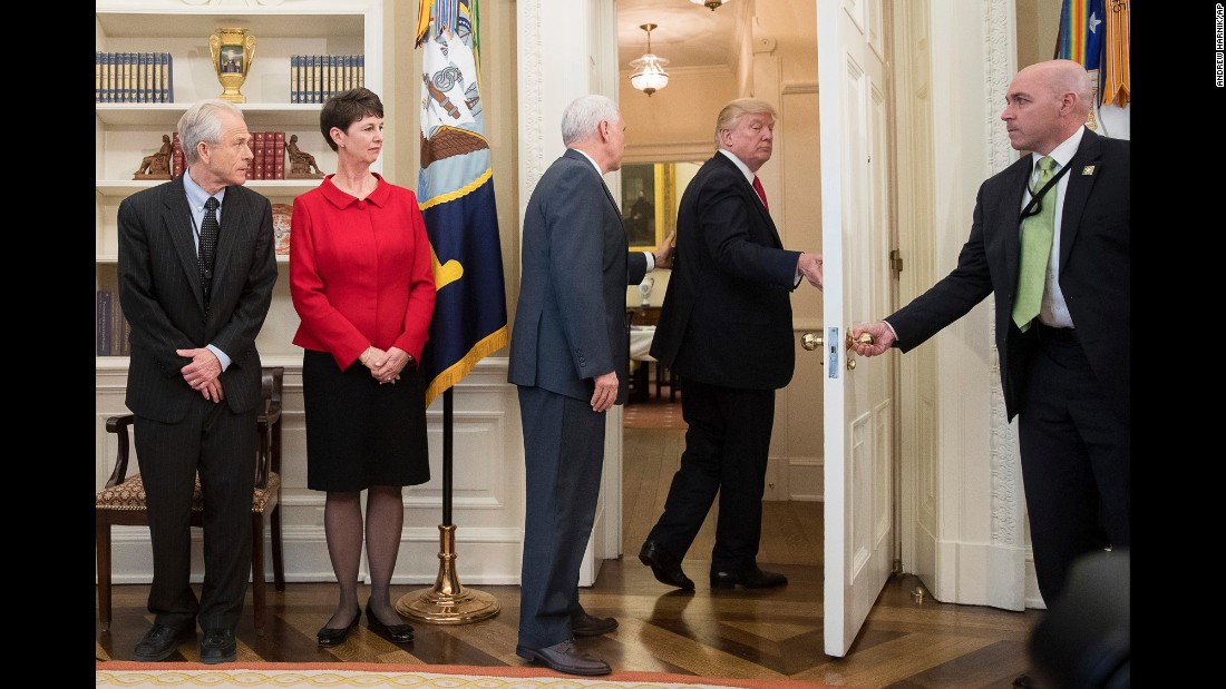 "Vice President Mike Pence, third from left, tries to stop Trump as Trump <a href=""http://www.cnn.com/2017/03/31/politics/donald-trump-executive-order-signing-walk-out/index.html"" target=""_blank"">walks out of an executive order signing ceremony</a> on Friday, March 31. During the signing ceremony, White House pool reporters asked Trump questions about former national security adviser Michael Flynn, who has offered to testify on Russian involvement in the US election. The President ignored the questions and moved to another room to sign the two executive orders, which regarded trade policy."