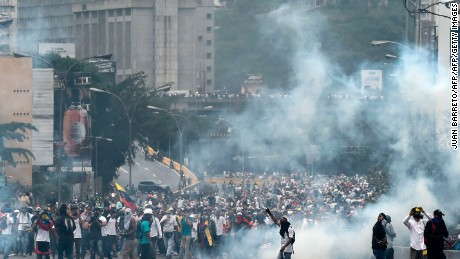 Demonstrators clash with the riot police during a protest against Venezuelan President Nicolas Maduro, in Caracas on April 20, 2017. Venezuelan riot police fired tear gas Thursday at groups of protesters seeking to oust President Nicolas Maduro, who have vowed new mass marches after a day of deadly unrest. Police in western Caracas broke up scores of opposition protesters trying to join a larger march, though there was no immediate repeat of Wednesday's violent clashes, which left three people dead. / AFP PHOTO / JUAN BARRETO        (Photo credit should read JUAN BARRETO/AFP/Getty Images)