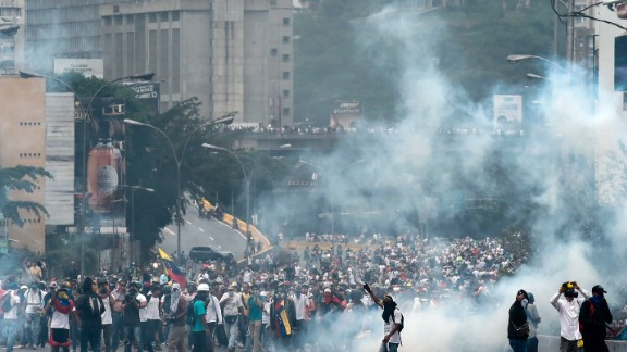 Demonstrators clash with the riot police during a protest against Venezuelan President Nicolas Maduro, in Caracas on April 20, 2017. Venezuelan riot police fired tear gas Thursday at groups of protesters seeking to oust President Nicolas Maduro, who have vowed new mass marches after a day of deadly unrest. Police in western Caracas broke up scores of opposition protesters trying to join a larger march, though there was no immediate repeat of Wednesday