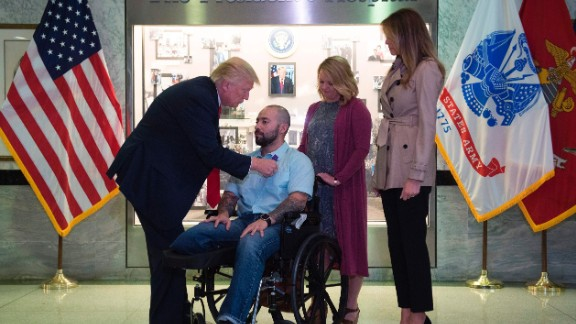 President Donald Trump awards the purple heart to Sergeant First Class Alvaro Barrientos.