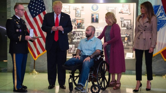 US President Donald Trump awards the purple heart to Sergeant First Class Alvaro Barrientos as first lady Melania Trump and Barrientos