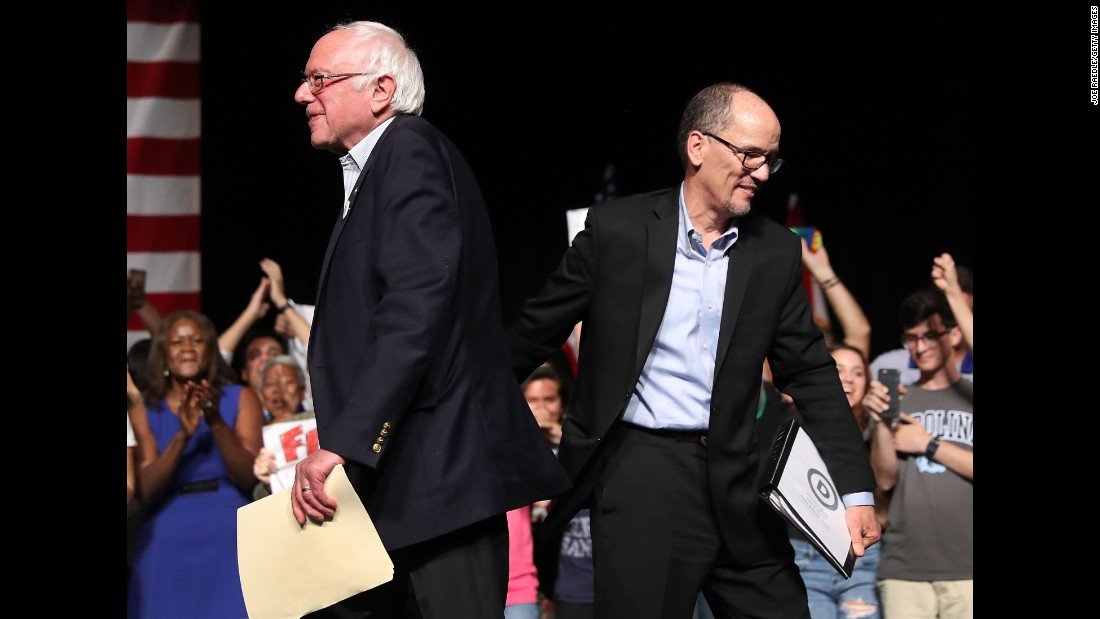 "Sen. Bernie Sanders and DNC Chair Tom Perez walk past each other as Sanders takes to the stage to speak during their ""Come Together and Fight Back"" tour at the James L Knight Center on Wednesday, April 19 in Miami, Florida. Sanders and Perez spoke on topics including raising the minimum wage to $15 an hour, pay equity for women, rebuilding the crumbling infrastructure and more."