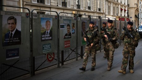 Army soldiers patrol past a polling station showing posters with faces of the candidates for the first-round presidential election in Paris, Sunday, April 23, 2017. French voters are casting ballots for their next president in an unusually close first-round election Sunday, after a campaign dominated by concerns about jobs and immigration and clouded by security fears following a recent attack on police guarding the Champs-Elysees in Paris. (AP Photo/Emilio Morenatti)