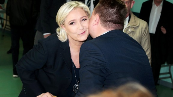 French presidential election candidate for the far-right Front National (FN - National Front) party Marine Le Pen kisses an electoral official at a polling station in Henin-Beaumont, north-western France, on April 23, 2017, during the first round of the Presidential election. / AFP PHOTO / joel SAGET        (Photo credit should read JOEL SAGET/AFP/Getty Images)