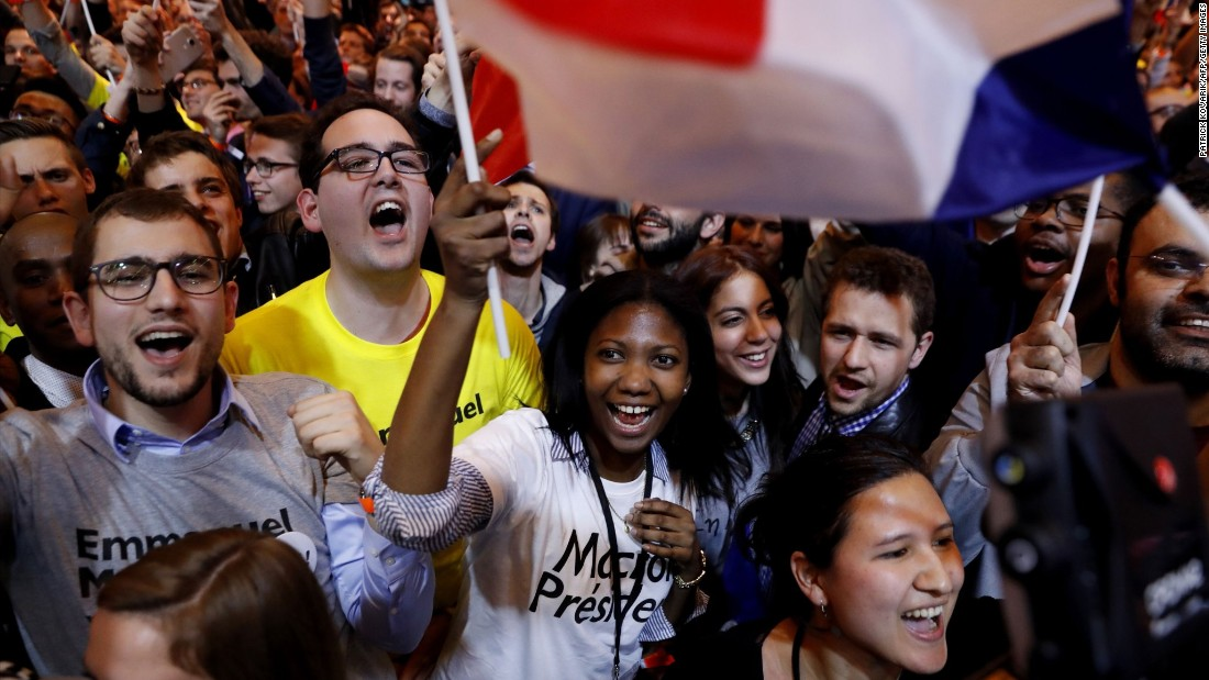 Supporters of Macron cheer in Paris after the announcement that he qualified for the runoff.