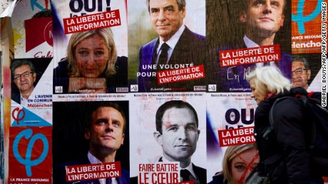 A woman walks past campaign posters for the candidates in the 2017 French presidential election in Paris.