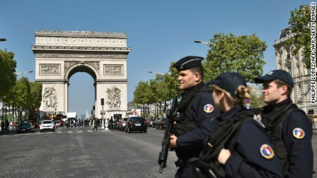 French Police officers patrol the Champs Elysees avenue near the Arc de Triomphe. A gunman opened fire on police on the avenue on April 21, killing one officer and wounding two others in an attack claimed by the Islamic State group